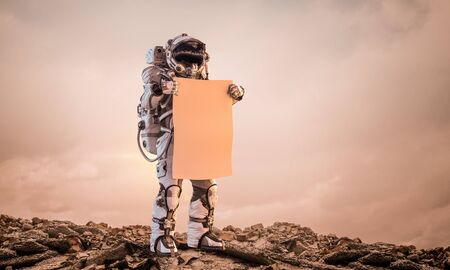 Martian on planet surface with carton banner in hands. Mixed media 版權商用圖片