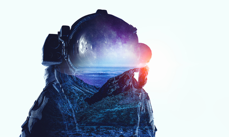 Double exposure of astronaut and natural landscape on white background. Mixed media