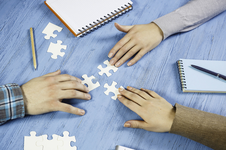 Group of people sitting at table and assembling jigsaw puzzle