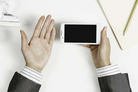 Top view of businesswoman hand with smartphone over white table Banque d'images