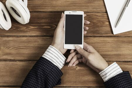Top view of businesswoman hand with smartphone over brown wooden table Banque d'images