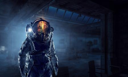 Astronaut explorer in dark interior. Mixed media Banque d'images