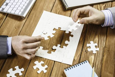 Business people sitting at table and assembling jigsaw puzzle
