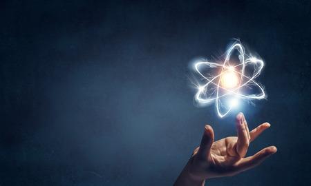 Human hand and atom molecule as science concept. 3d rendering Archivio Fotografico