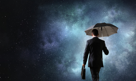 Back view of businessman with black umbrella on dark night sky 스톡 콘텐츠