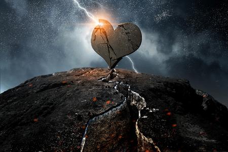 Gebrochenes Herz aus Stein auf Felsen. Gemischte Medien