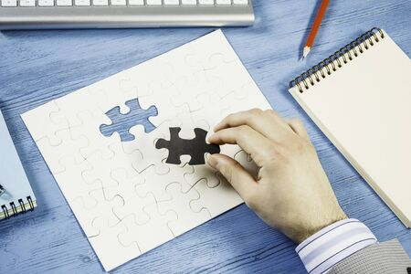 Hand of businessman sitting at table and assembling jigsaw puzzle