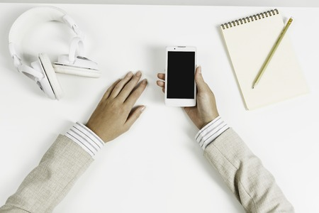 Top view of businesswoman hand with smartphone over white table Stock Photo