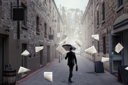 Businessman with black umbrella walking on city street. Mixed media Stock Photo