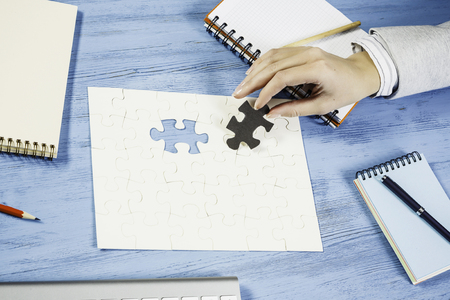 Hand of businesswoman sitting at table and assembling jigsaw puzzle