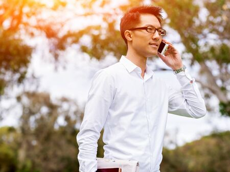 Businessman portrait with mobile phone outdoors