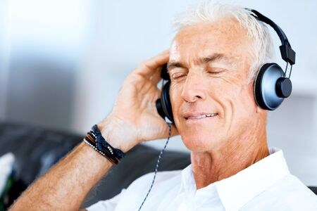 Handsome gray haired senior man with headphones