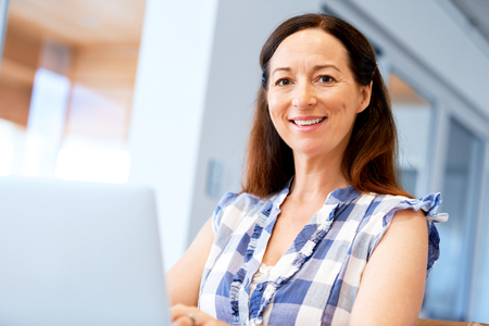 Mature beautiful woman working on her laptop 스톡 콘텐츠