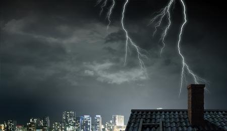 Bright lightning striking roof of house. Mixed media