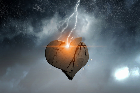 Broken heart of stone on rock top. Mixed media