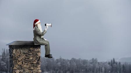 Santa Claus on rooftop . Mixed media Stock Photo