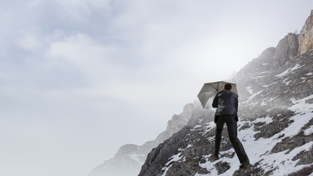 Businessman with black umbrella among snowy mountains ready to overcome any challenge. Mixed media Archivio Fotografico - 97771069
