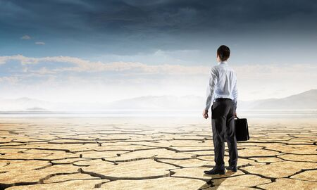 Businessman with suitcase in dry cracked desert Imagens
