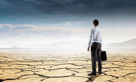 Businessman with suitcase in dry cracked desert Standard-Bild