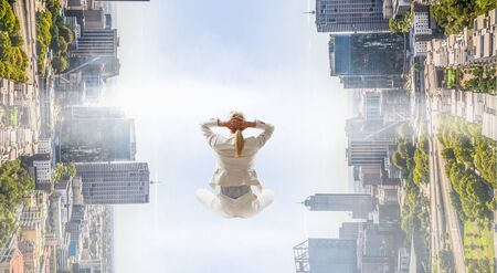 Businesswoman sitting in lotus pose on cloud high in sky