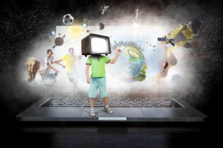 Muchacho del cabrito con el monitor de la televisión para sus técnicas de juego mixta Foto de archivo - 98001662