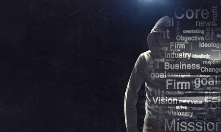 暗い背景にフーディを身に着けている犯罪者の男。混合メディア 写真素材