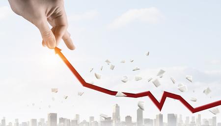 収入の概念として赤い矢印を引き上げる手。混合メディア 写真素材