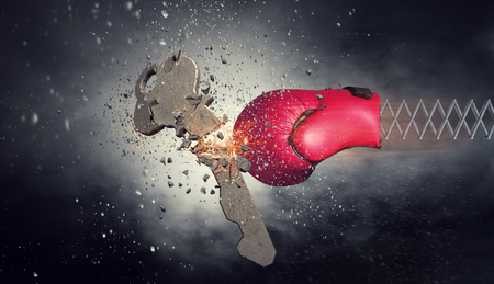 Red boxing glove on spring breaking concrete key. Mixed media 写真素材