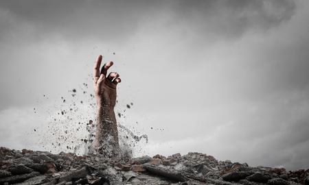 main sortant du sol comme concept pour ne jamais abandonner