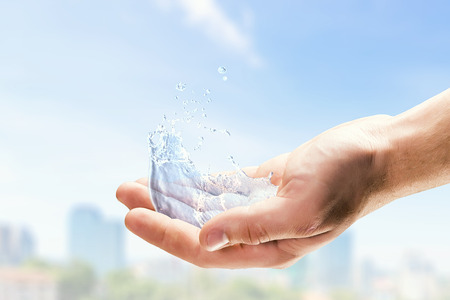 Close of person hands holding water splashes