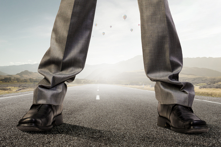 Legs of giant businessman standing on asphalt road. Mixed media