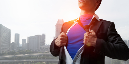 Young businessman showing superhero suit underneath his shirt standing against city background