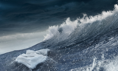 Ice block floating on stormy sea waves Imagens