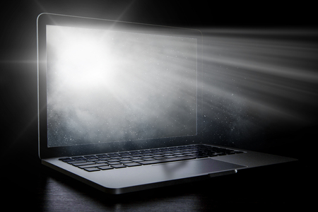 Open laptop with light coming from screen on dark background. Mixed media