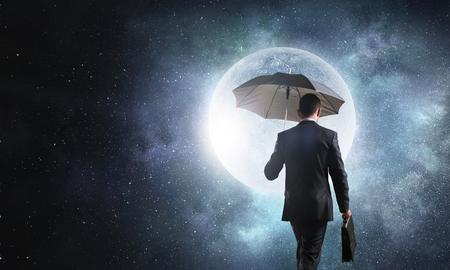 Back view of businessman with black umbrella on dark night sky 스톡 콘텐츠