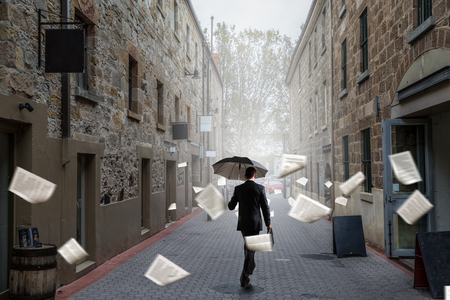 Businessman with black umbrella walking on city street. Mixed media Stok Fotoğraf