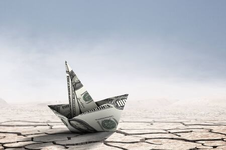 Dollar banknote ship in desert as symbol for financial crisis . Mixed media Stockfoto