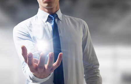 Close of businessman hand and light glowing in palm