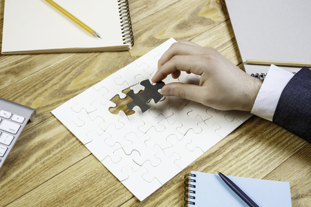 Hand of businesswoman completing puzzle with missing piece
