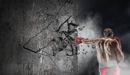 Young boxer man crashing concrete wall. Mixed media