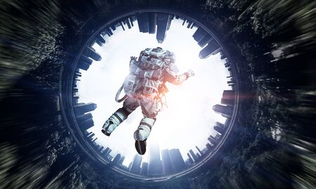 Astronaut floating in sky above modern cityscape