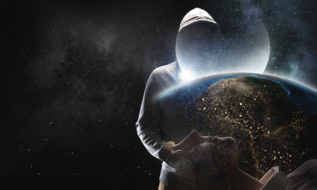 Criminal man wearing hoody against dark background. Mixed media. Elements of this image are furnished by NASA