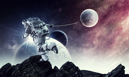 Fantasy image with spaceman catch planet. Mixed media 写真素材