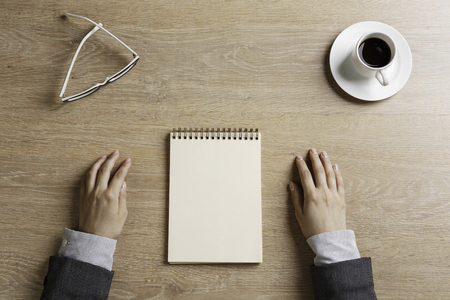 Top view of businesswoman sitting at wooden table with pen and notepad in hands