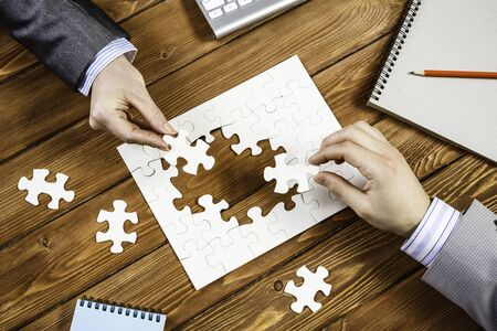 Hand of businesspeople completing puzzle with missing piece