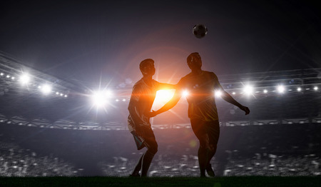 Soccer players at sport stadium fighting for ball . Mixed media Stok Fotoğraf