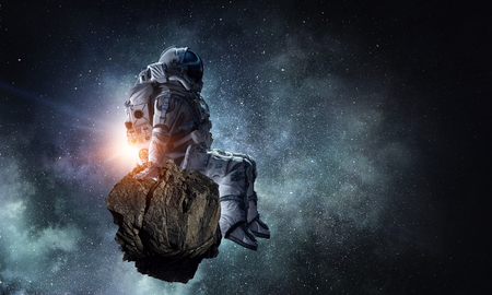 Astronaut sitting on cliff edge against dark starry sky. Mixed media