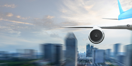 Wing and jet engine of airplane over sky. Mixed media Stock Photo