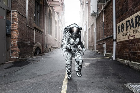 Astronaut in space suit running on road of city. Mixed media