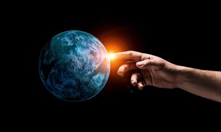 Cerca de la mano tocando con el planeta dedo